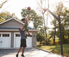 A father helping his daughter make a basket in a backyard court
