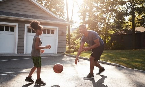 A father passing a basketball to his daughter