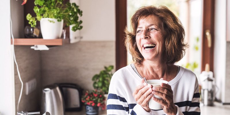 An older woman laughs while looking outside and holding a coffee mug