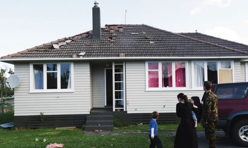 A wind damaged home with missing shingles and debris on the lawn