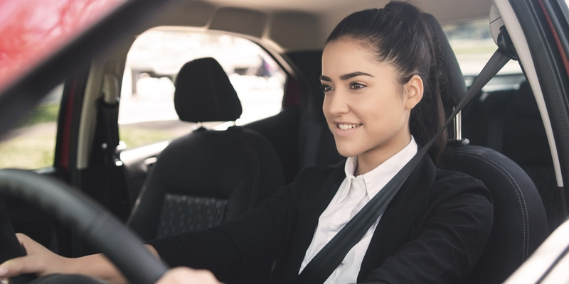 A young woman sits in the driver's seat of a car