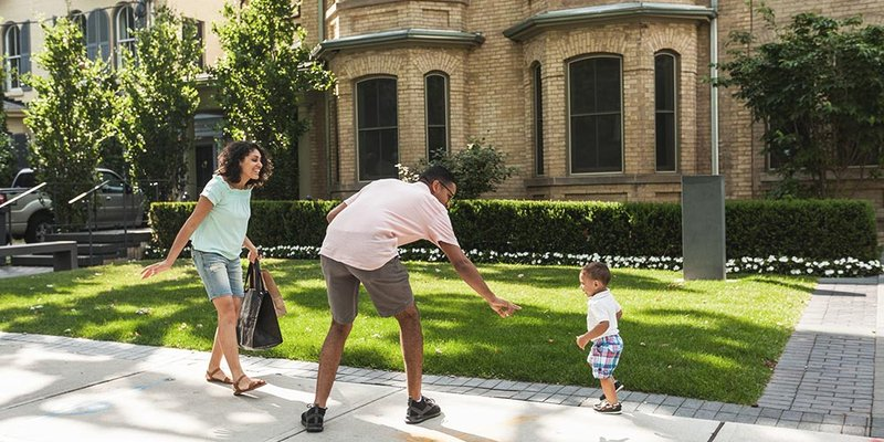 Father playfully reaches for his son while young family is walking outside in residential toronto neighbourhood