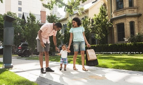 Young family walking on sidewalk in residential neighbourhood after a day of downtown shopping